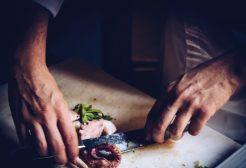 mezczyzna kroi nożem ośmiornice